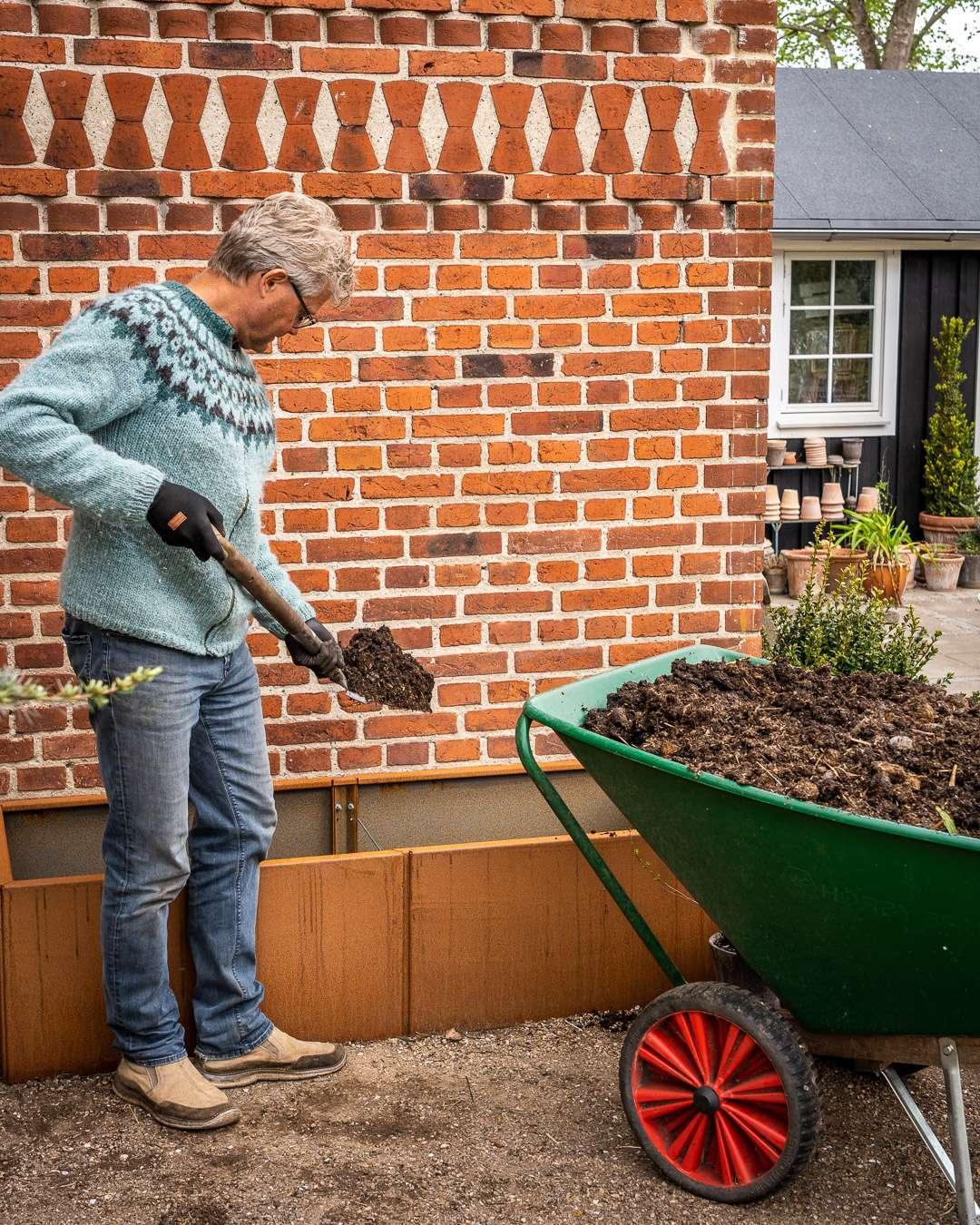 Kenn Römer-Bruhn fylder kompost fra haven i et højbed af cortenstål
